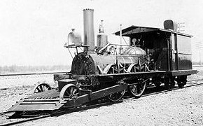 "Old photograph, steam locomotive named ""John Bull"" with huge cow-catcher and front end leader wheels."